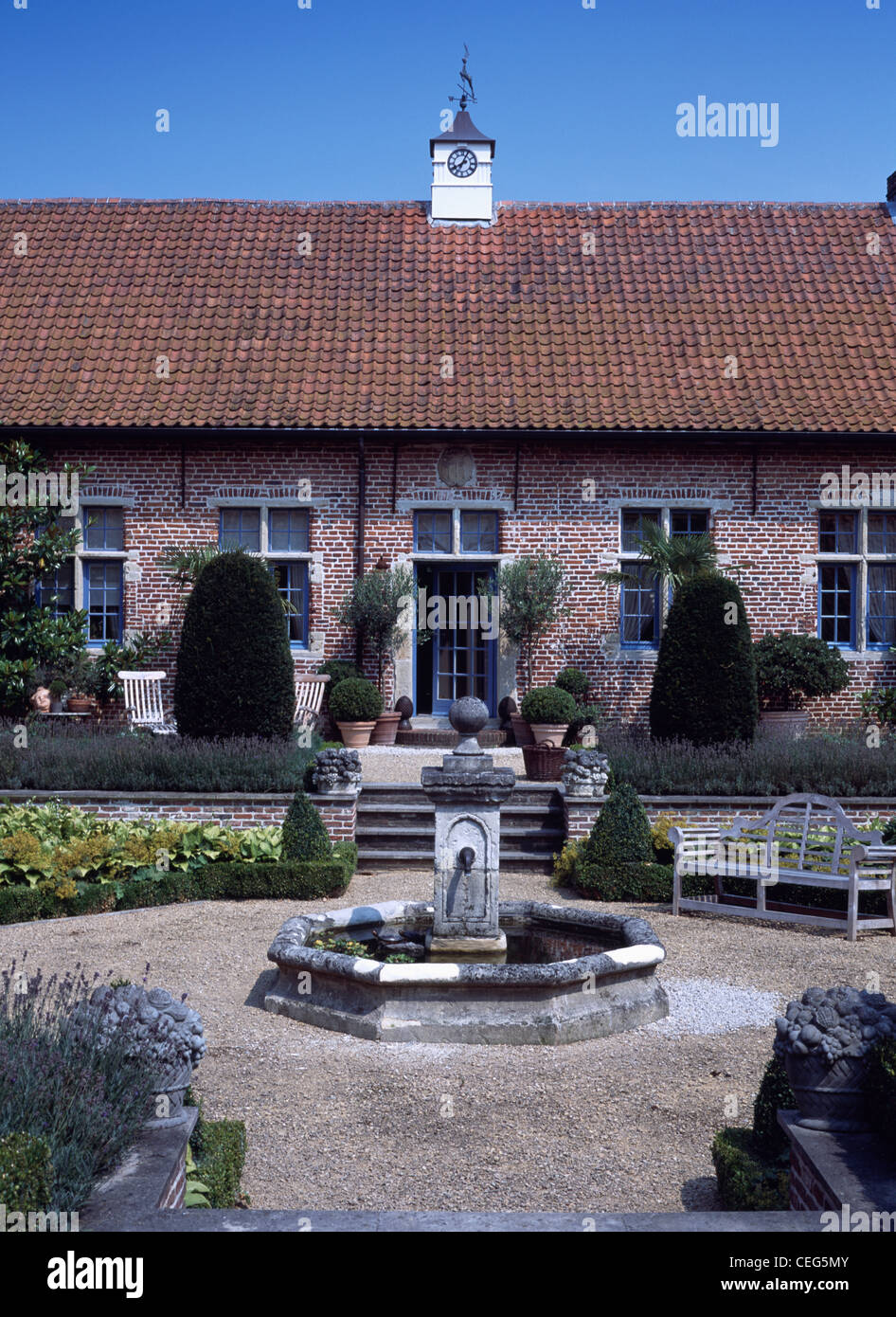 Stone Fountain In Small Pool In Formal Gravel Garden With Lavender Hedge In  Front Single Story Coach House With Clock Tower
