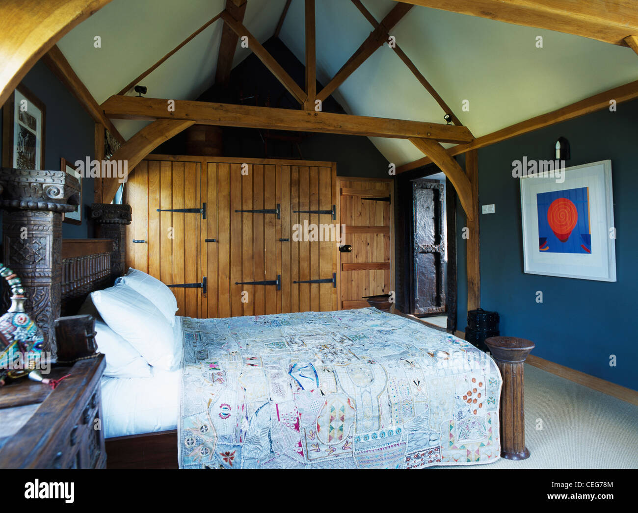 Built In Wardrobes With Unpainted Wooden Doors In Dark Blue Bedroom With  Exposed Wooden Beams And Carved Wooden Bed