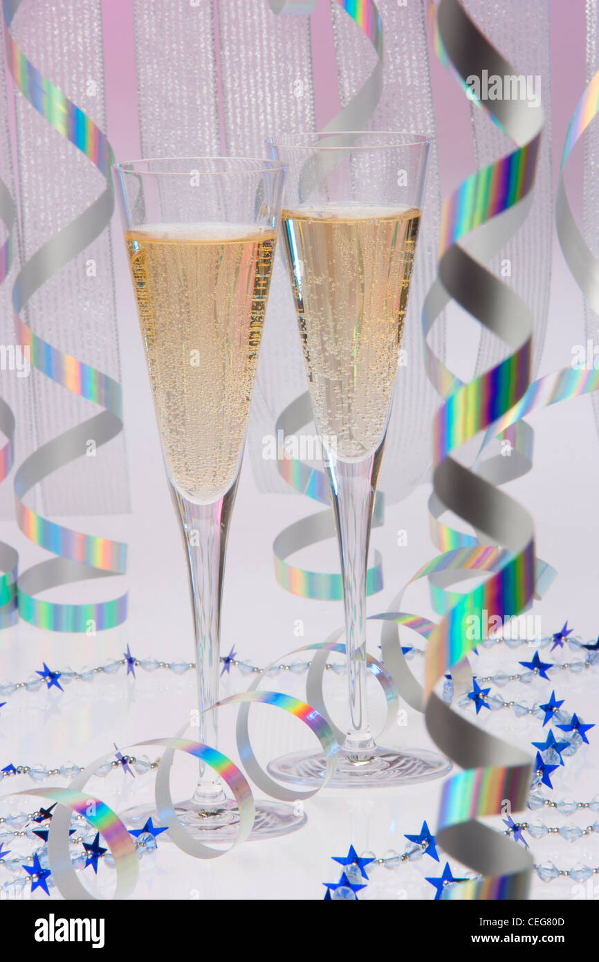 Two Champaign flutes with party decorations - Stock Image