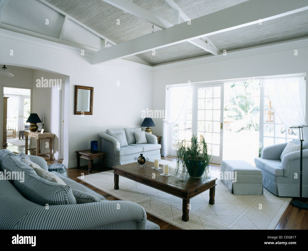 White living room in Barbados with pale blue sofa and chairs and ...