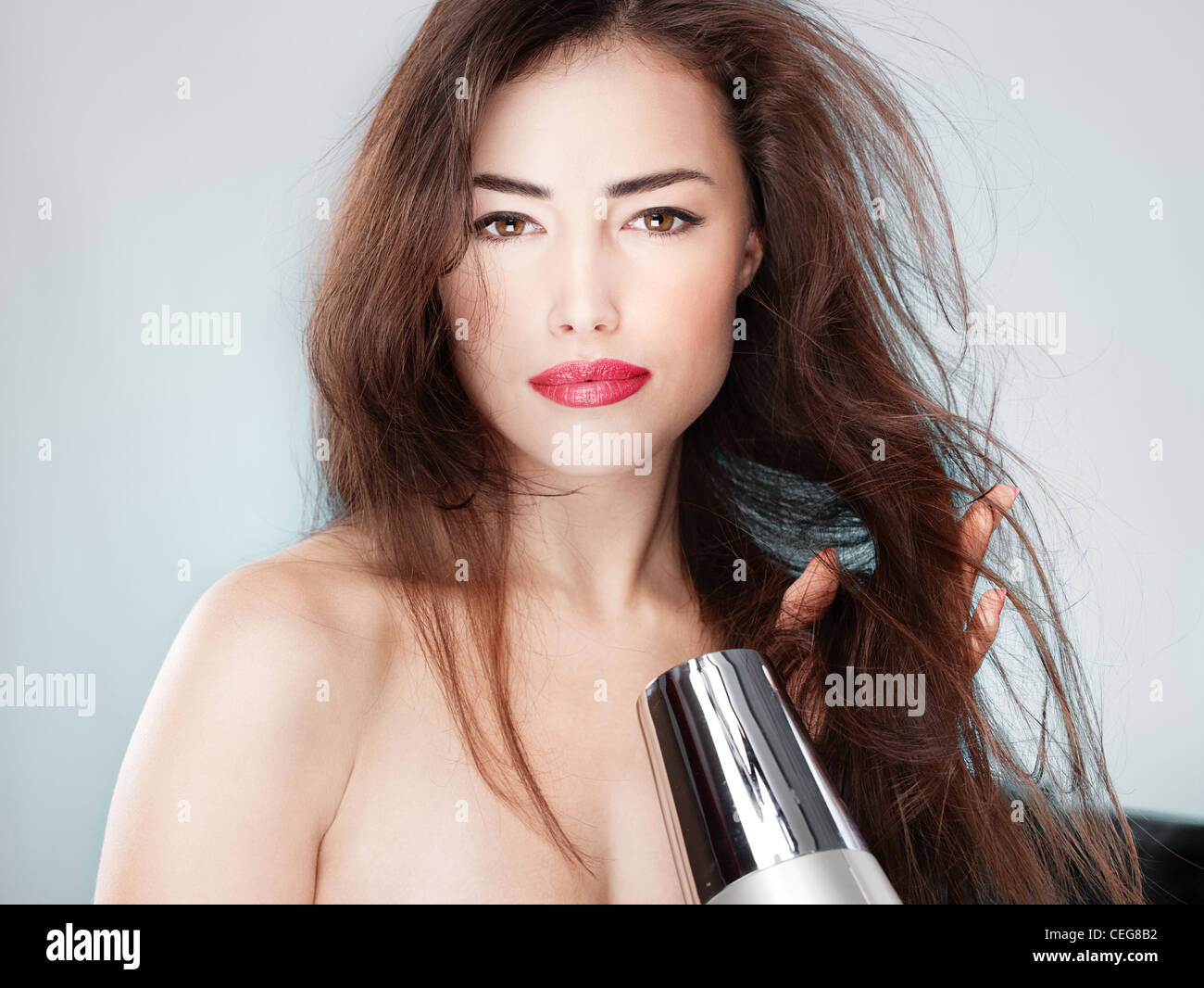 woman with long hair holding blow dryer - Stock Image