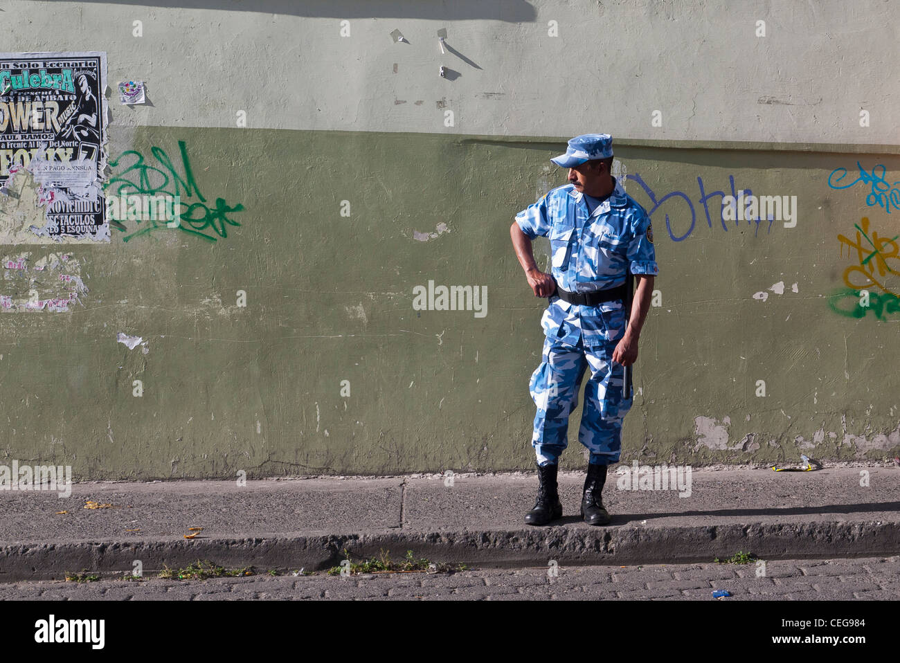 A Guatemalan military man in blue and white uniform stands on the sidewalk in Latacunga, Ecuador. Stock Photo