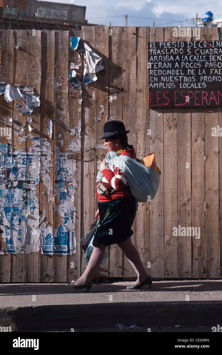 A 20-25 year old indigenous Indian in traditional dress walks in late afternoon on sidewalk in Latacunga, Ecuador. - Stock Image