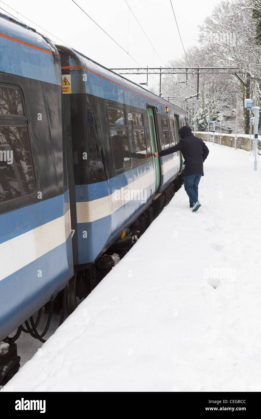 A passenger boarding a train at a railway station on a snowy day, London, UK - Stock Image