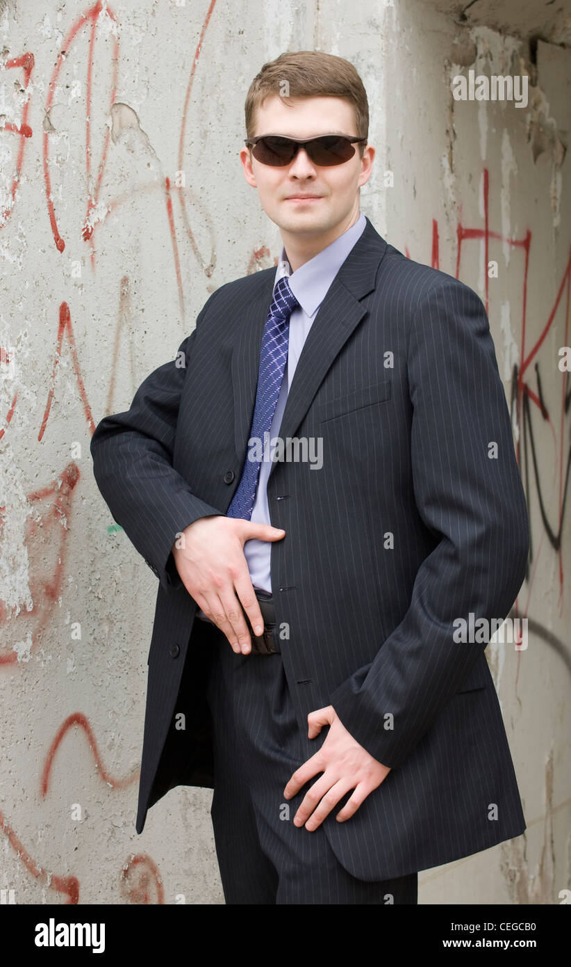 gangster or security man is ready to pull the gun from behind a belt