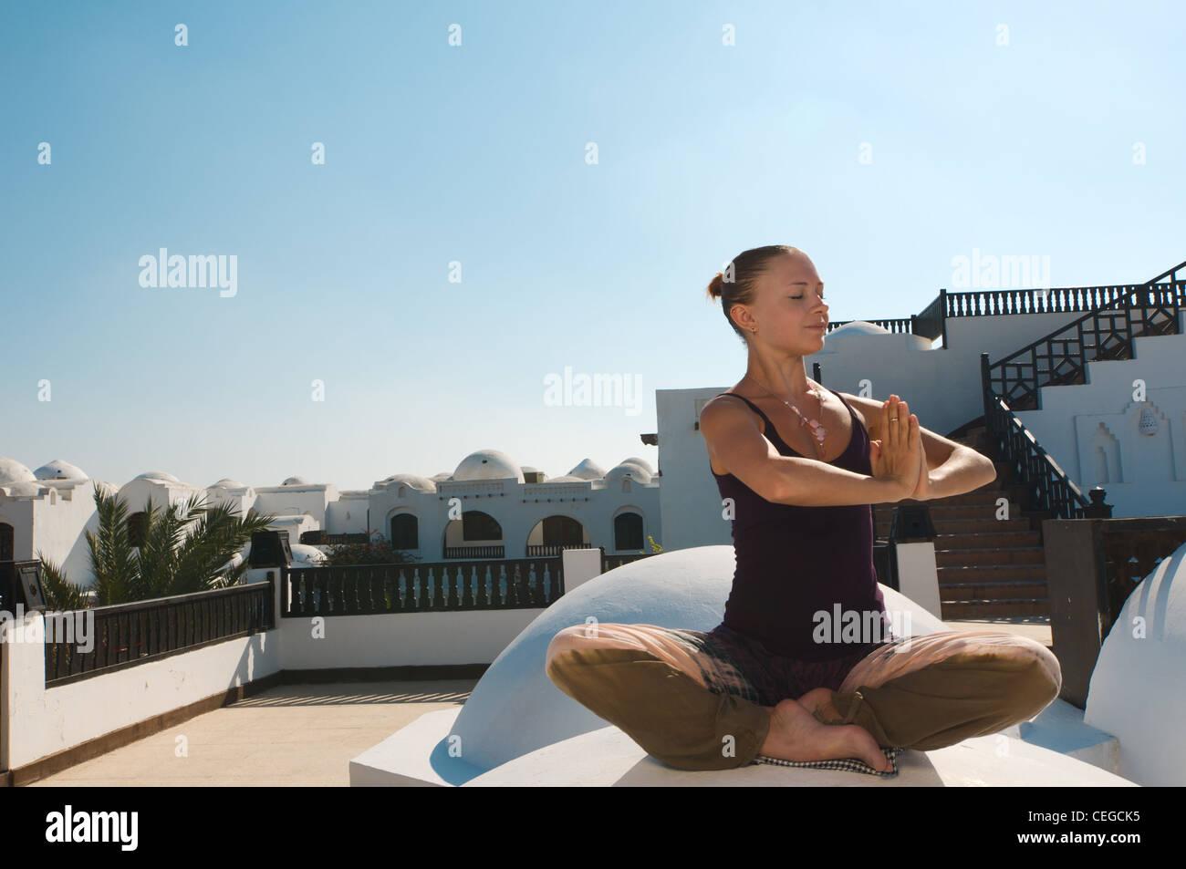 Attractive redhair woman practicing Vinyasa yoga outdoors - Stock Image
