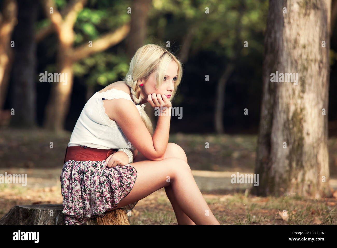 Beautiful young woman sitting on a trunk of a tree and thinking on something - Stock Image