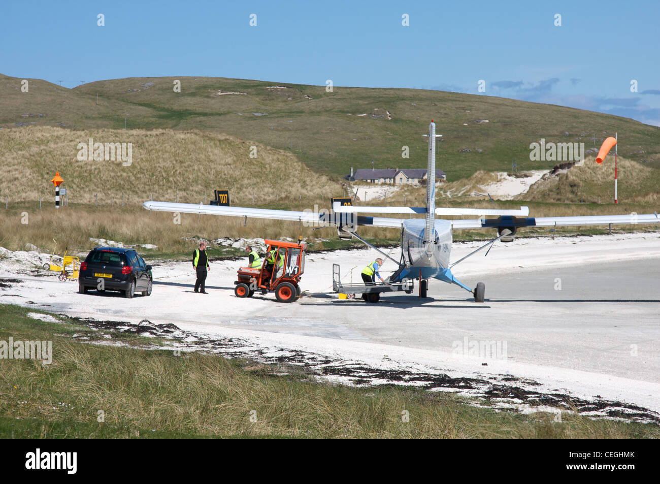 Collecting the luggage from a plane on Traigh Mhor beach, Barra airport, Outer Hebrides, Scotland, UK - Stock Image
