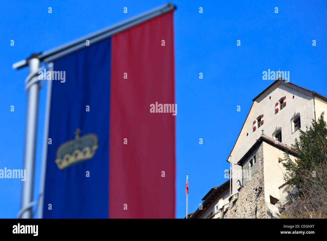 The official flag of Liechtenstein in the foreground and Vaduz castle in the background, Liechtenstein - Stock Image