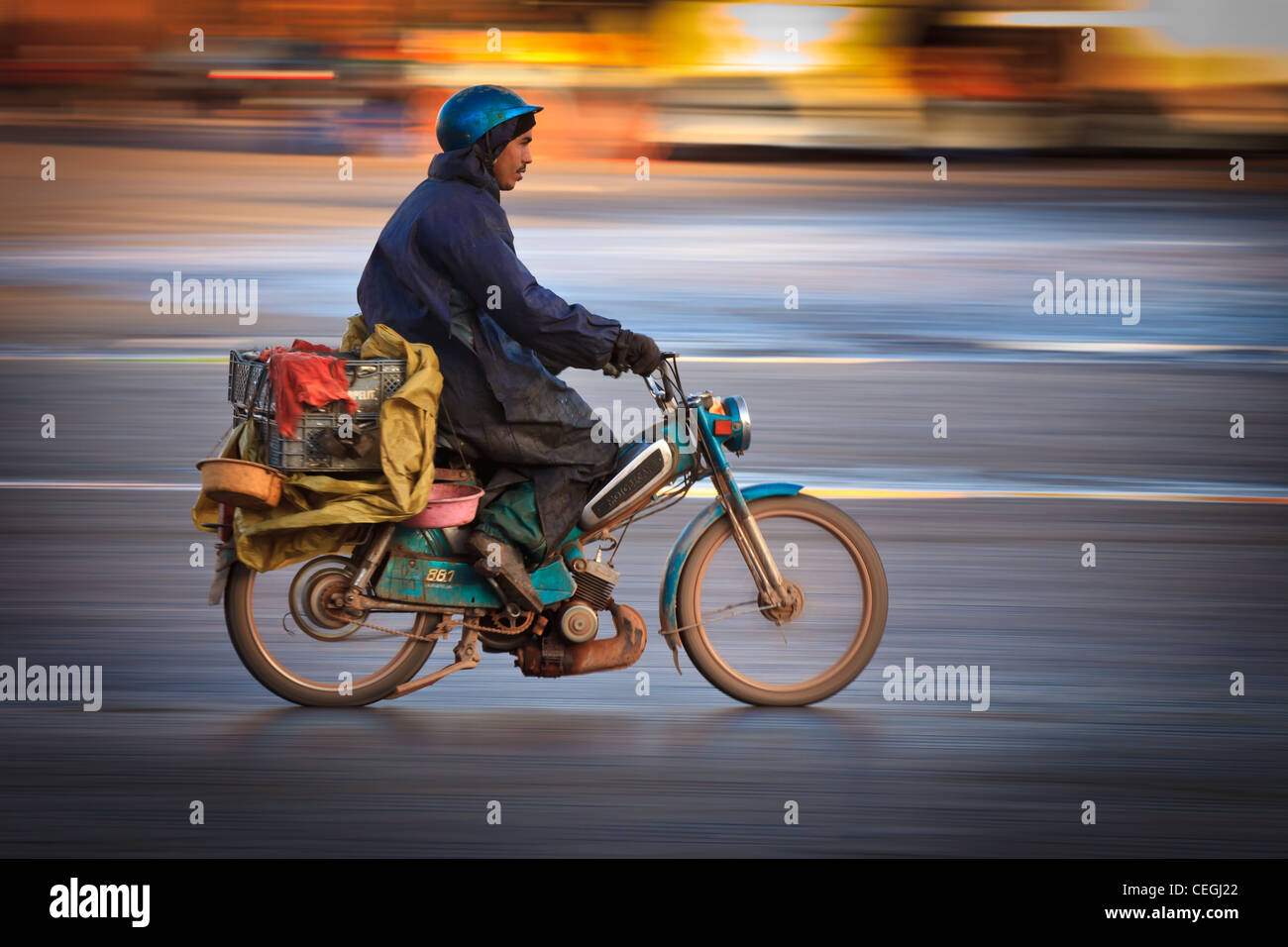 A man rides a moped in the morning light, Marrakesh, Morocco - Stock Image