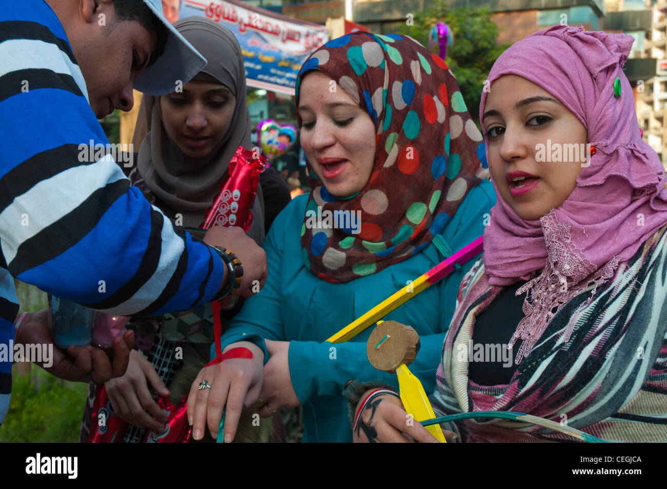 Teenaged girls receive face paint in the national colours at Eid el Adha celebrations in Cairo, Egypt. - Stock Image