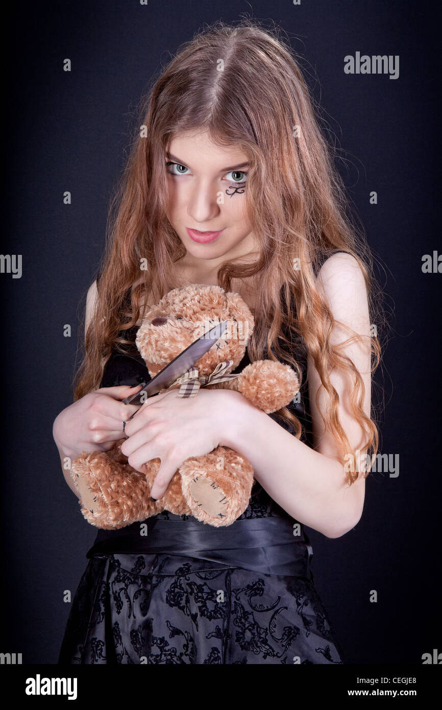 Beautiful violent girl destroying toy - Stock Image