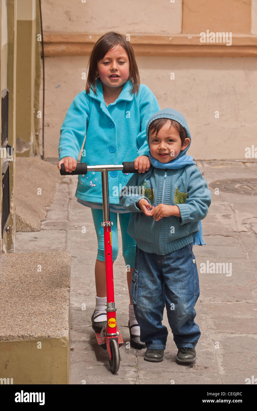 71d0c6a3 A 10-12 year old Ecuadorian girl and her 4-5 year old brother ride a Razor  scooter outside their home in Latacunga, Ecuador.