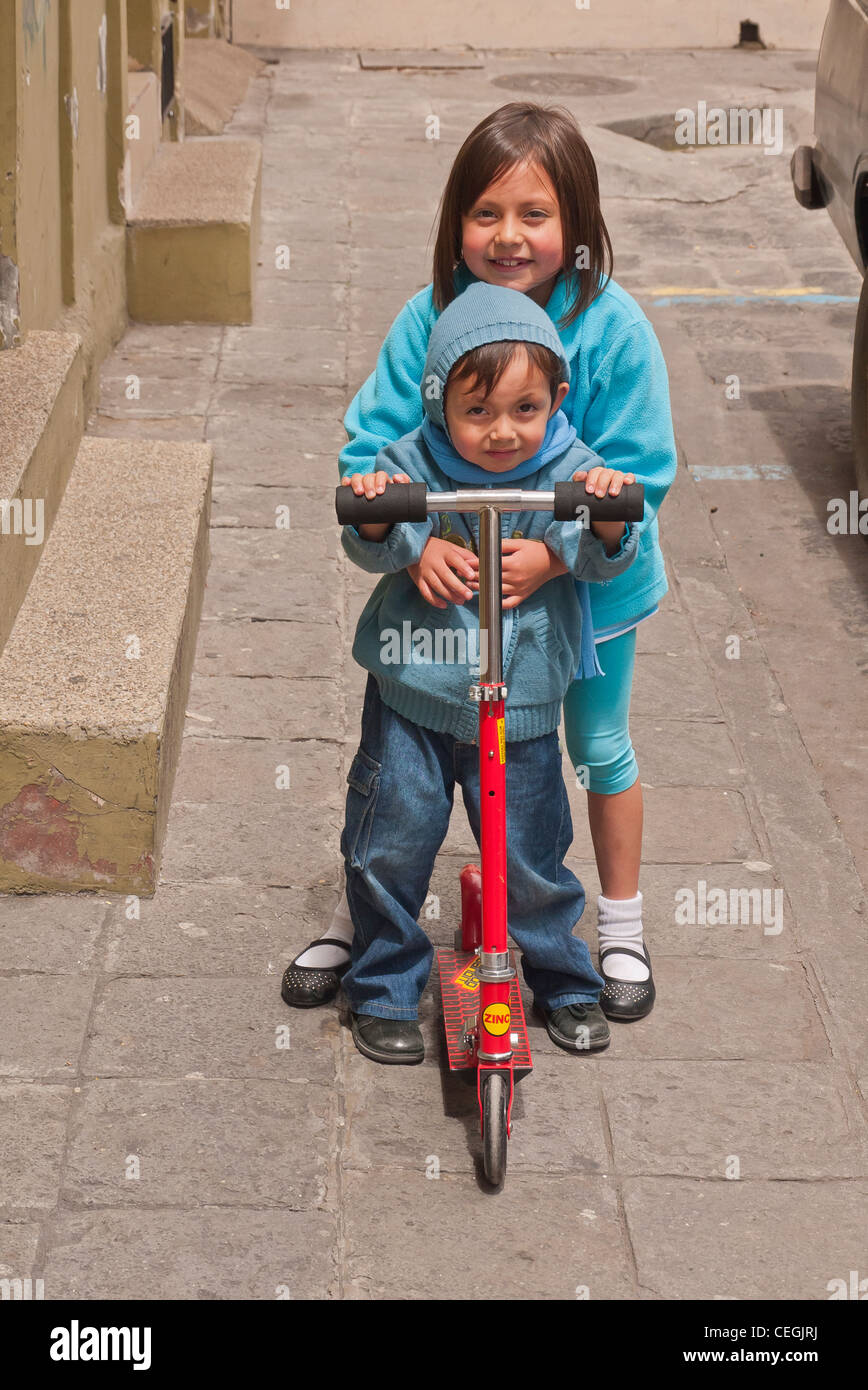 A 10-12 year old Ecuadorian girl and her 4-5 year old brother ride a ...