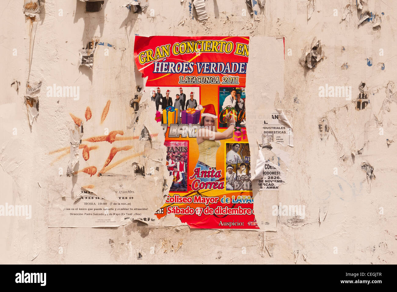 A tattered red wall concert poster for a 'gran concierto' for 'Heros Verdade' in Latacunga, Ecuador. - Stock Image