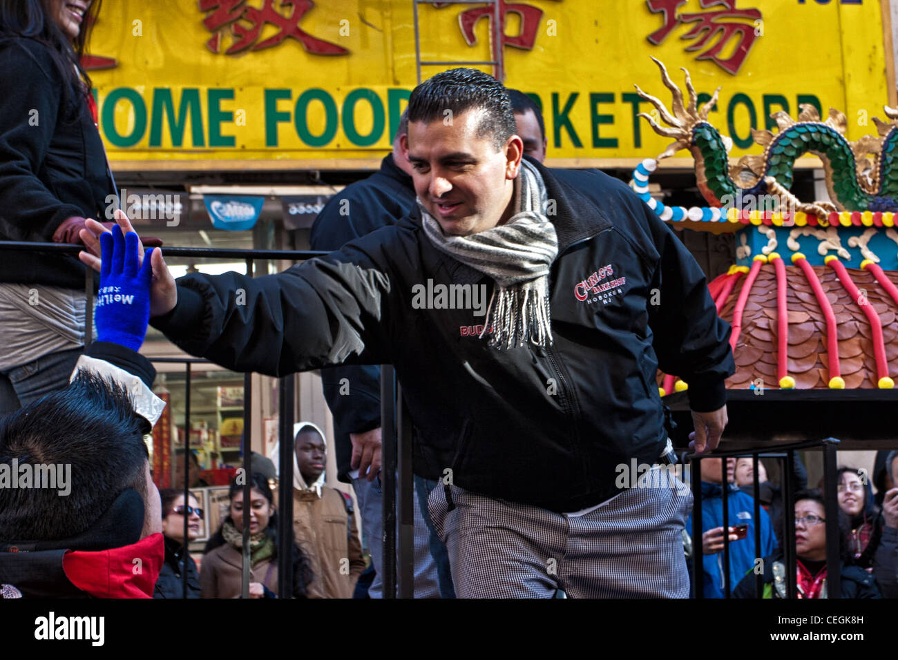 Cake Boss Buddy Valastro gives a high five to a fan at the 2012 Lunar New Year Parade in New York City's Chinatown. - Stock Image