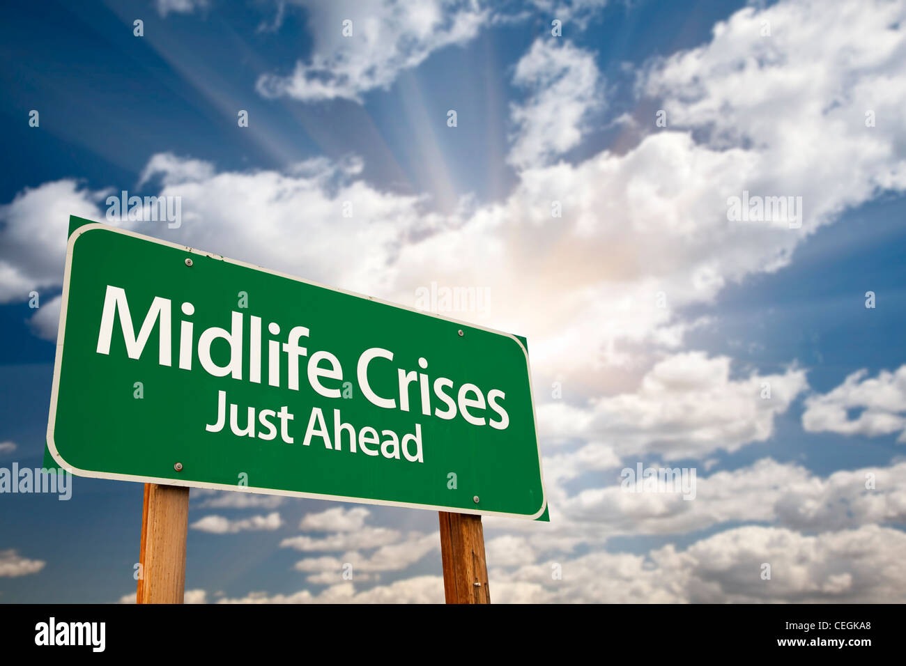 Midlife Crises Just Ahead Green Road Sign with Dramatic Clouds, Sun Rays and Sky. - Stock Image