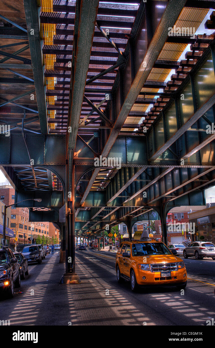 Taxi Cab driving under elevated train - Stock Image