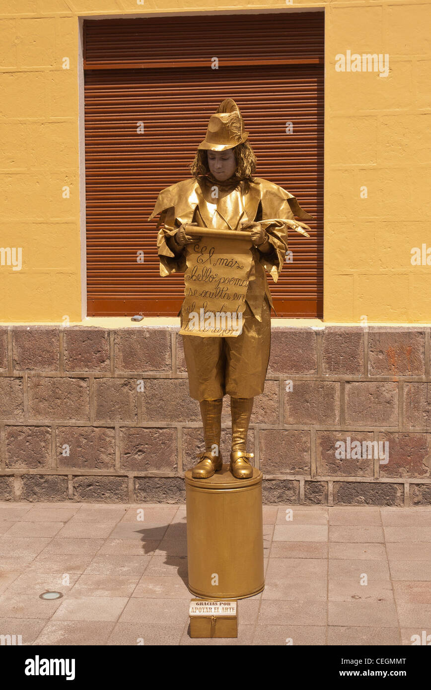 A 20 year old male mime street performer in gold body paint and gold clothing performs in Latacunga, Ecuador. - Stock Image