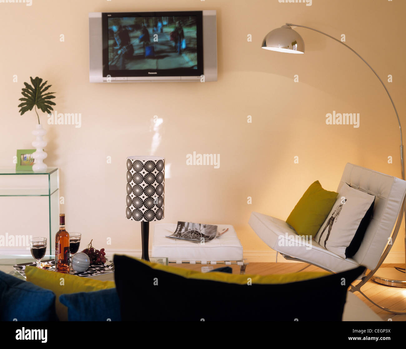 Lounge with wall mounted TV and standing lamp. - Stock Image