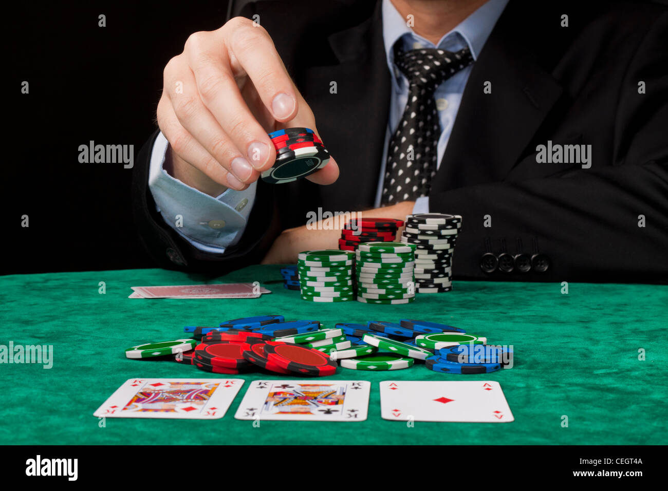 A businessman placing a bet in a Texas hold 'em poker game. - Stock Image