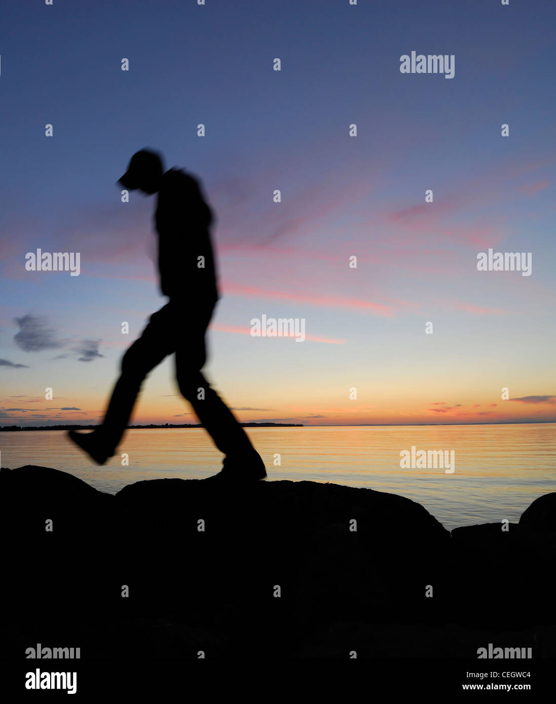 Silhouette of man walking by a lake at night - Stock Image