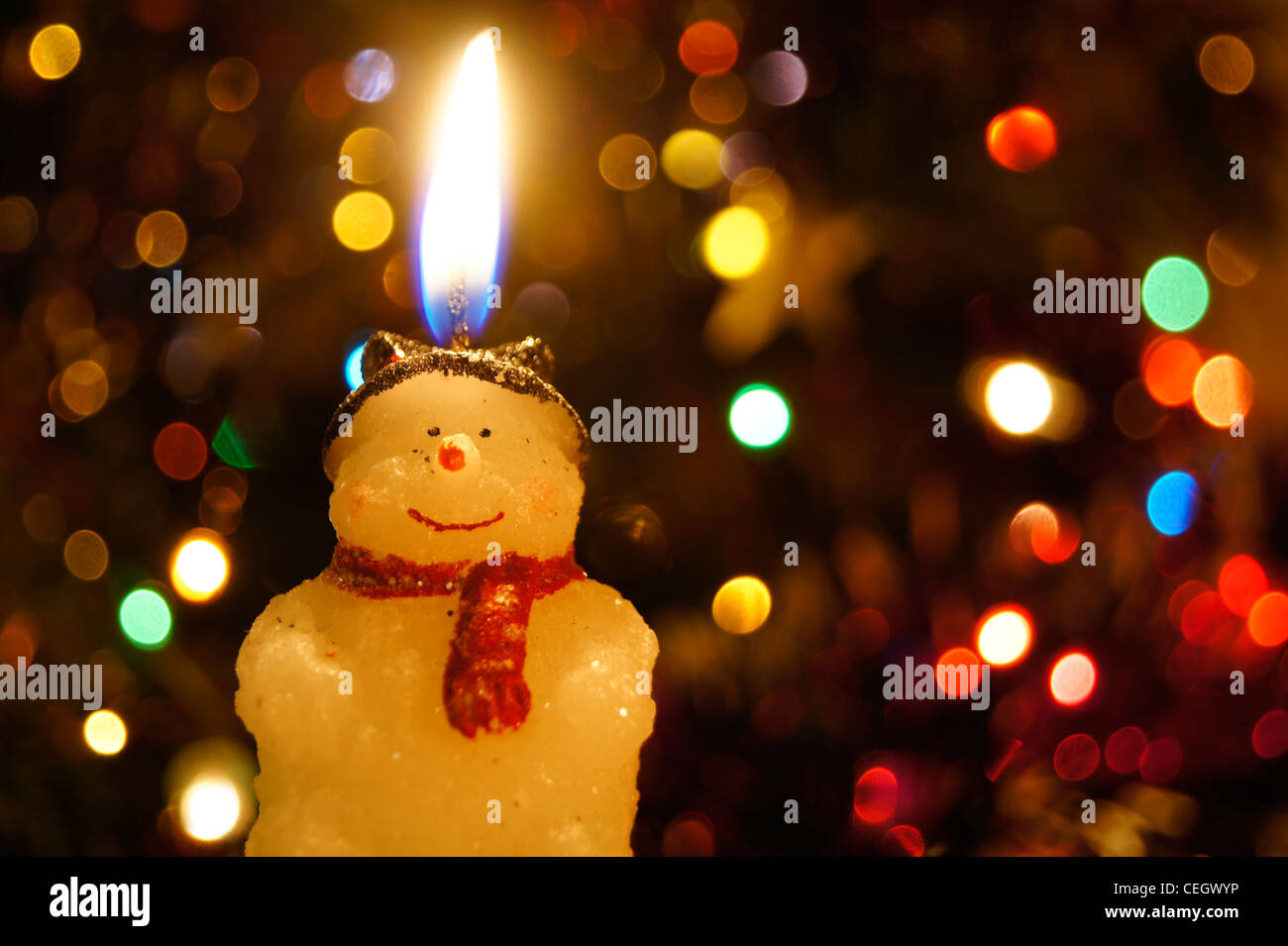 a snowman candle flame on a blurry christmas light background