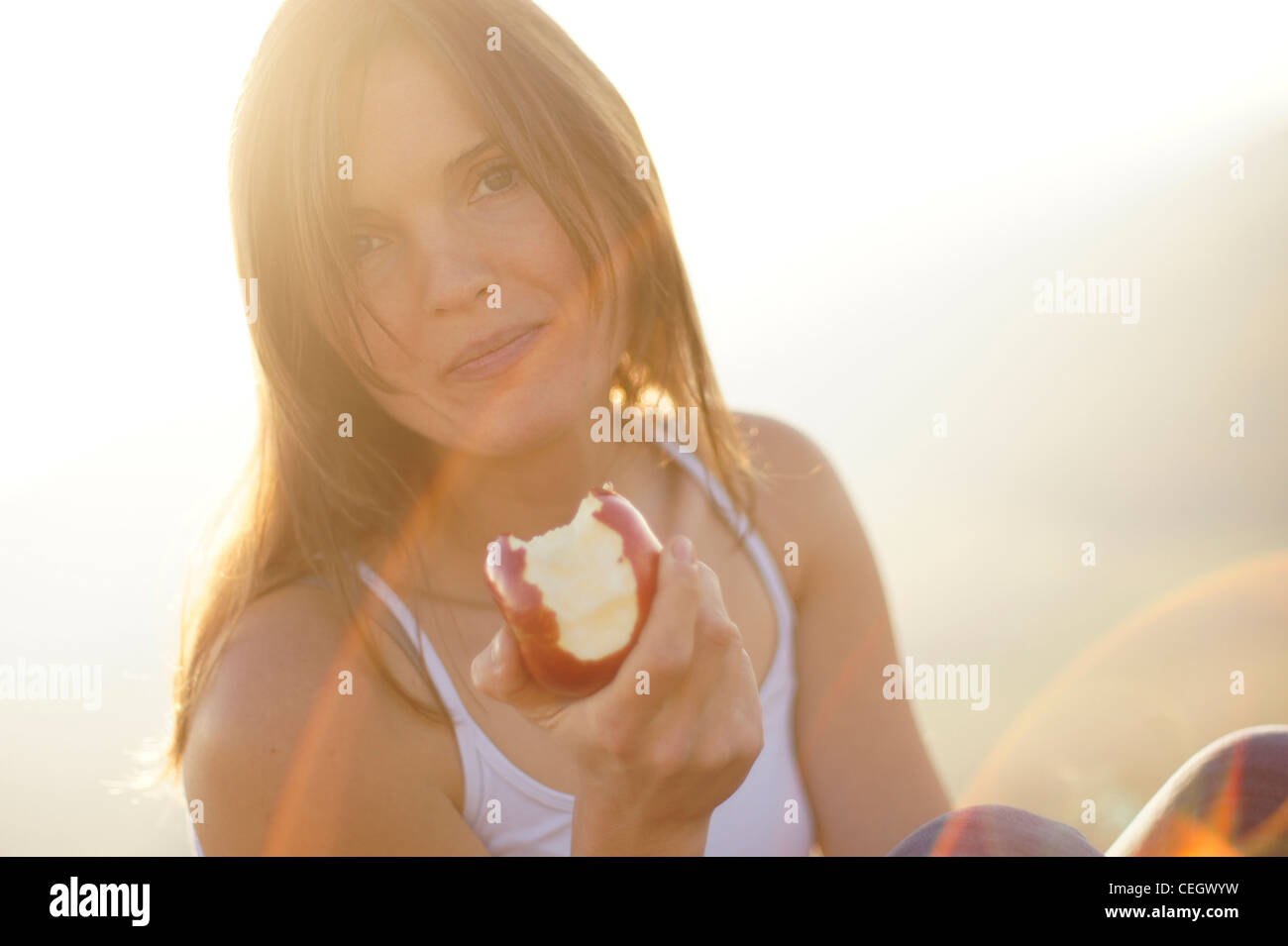Beautiful young woman eating a juicy red apple in the beautiful golden light of the setting sun - Stock Image