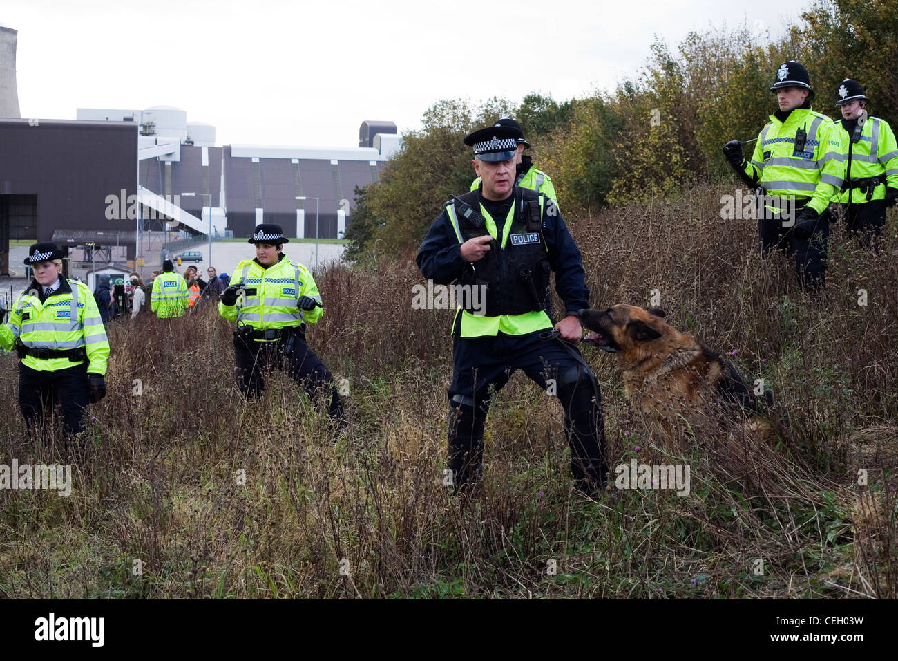 Police Officer with dog forming a kettle at Ratcliffe on Soar Power Station Climate Swoop Protest. - Stock Image