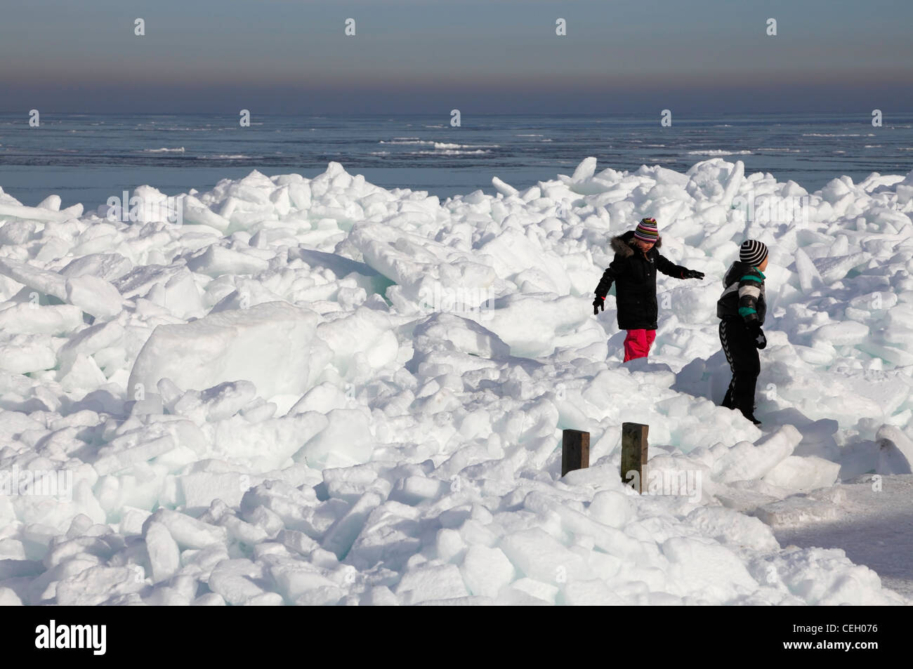 Two kids on ice packs in the Øresund  or Oresund sound at Rungsted Harbour near Copenhagen after a cold spell - Stock Image
