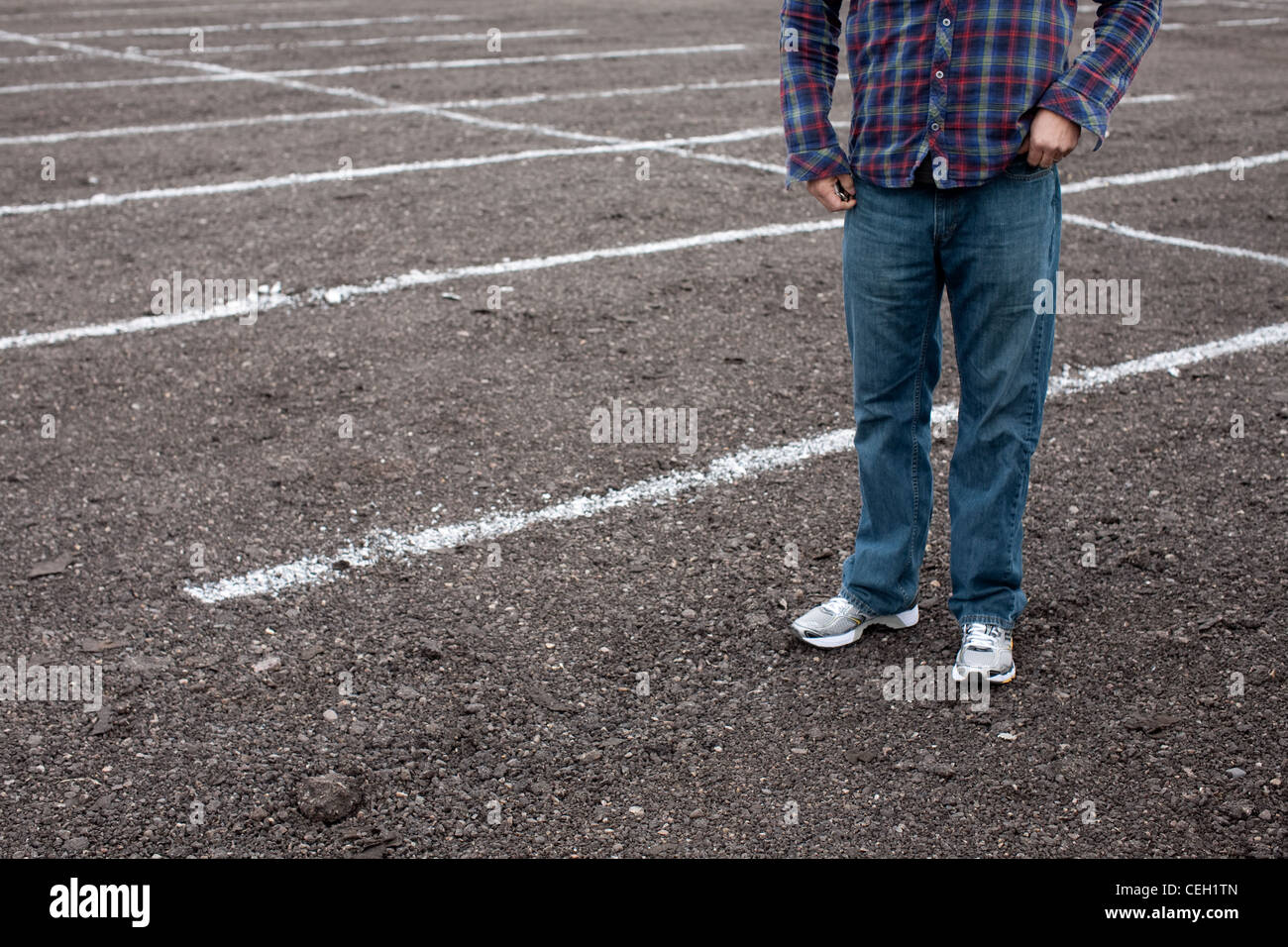 Anonymous man standing in empty parking lot - Stock Image