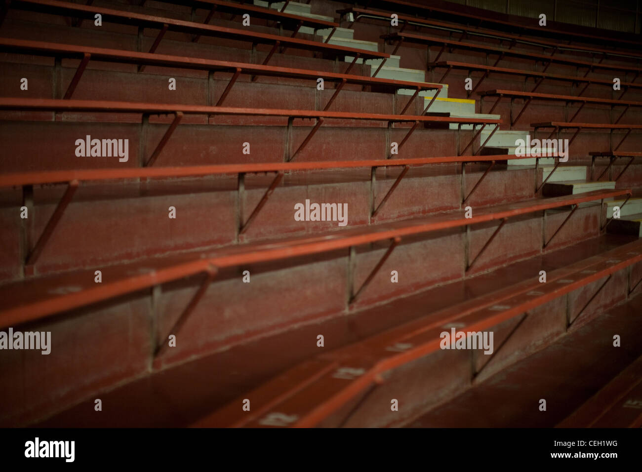 Empty bleacher grandstand rows of seats in a large auditorium - Stock Image