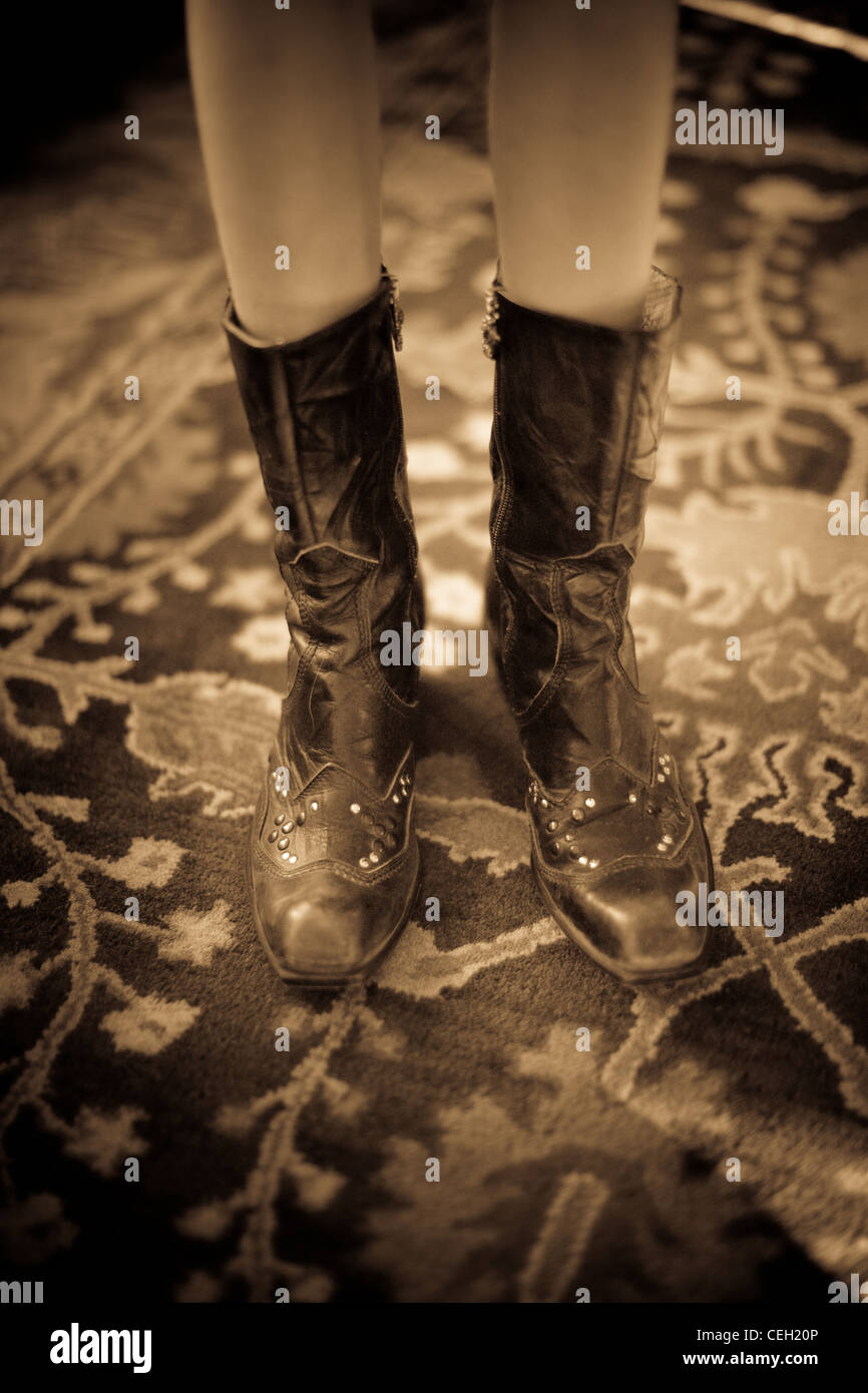 Close up of a girl wearing cowboy boots, sepia - Stock Image