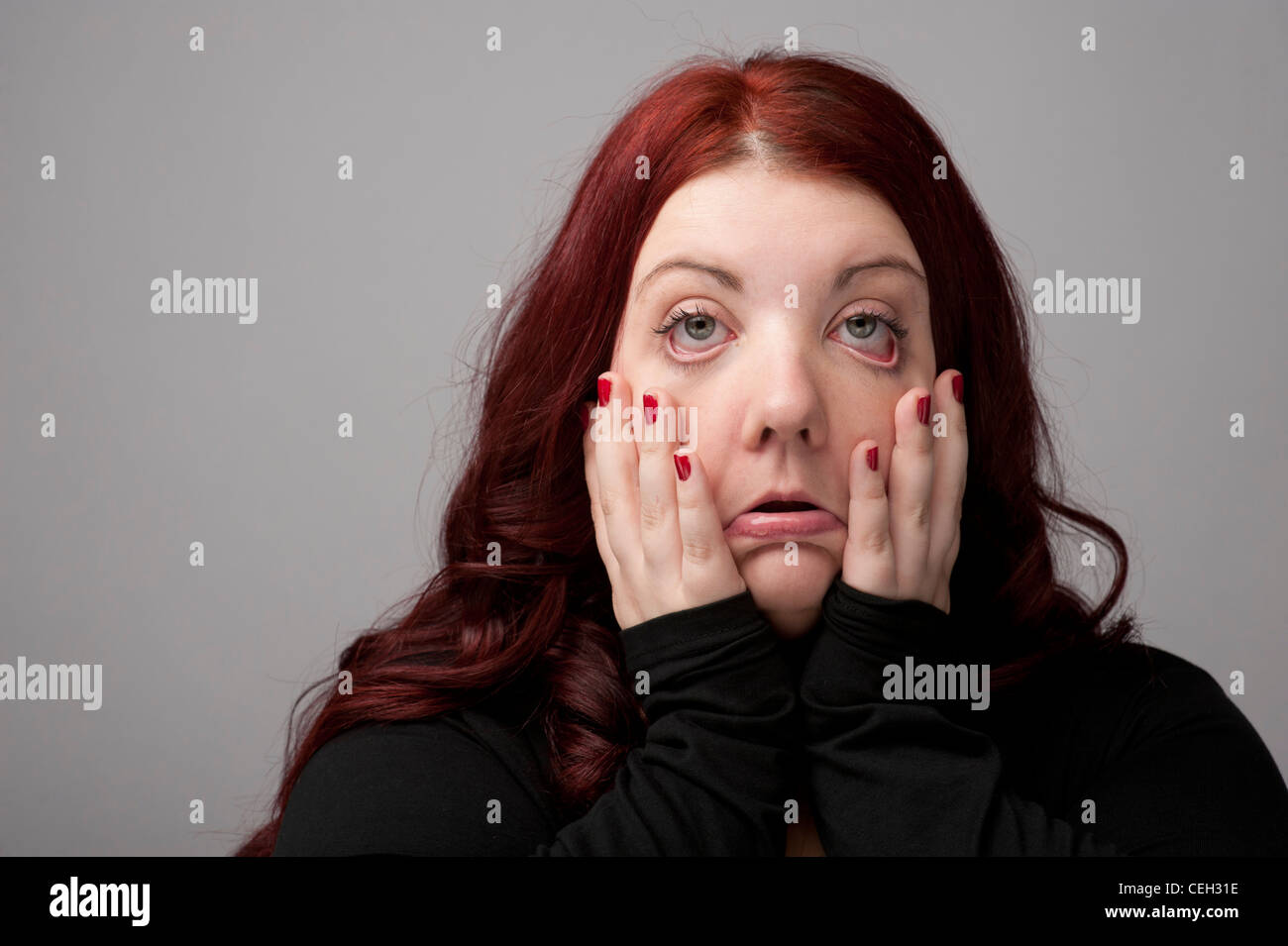 A auburn haired caucasian woman looking and feeling ill sick poorly hungover with bleary eyes - Stock Image