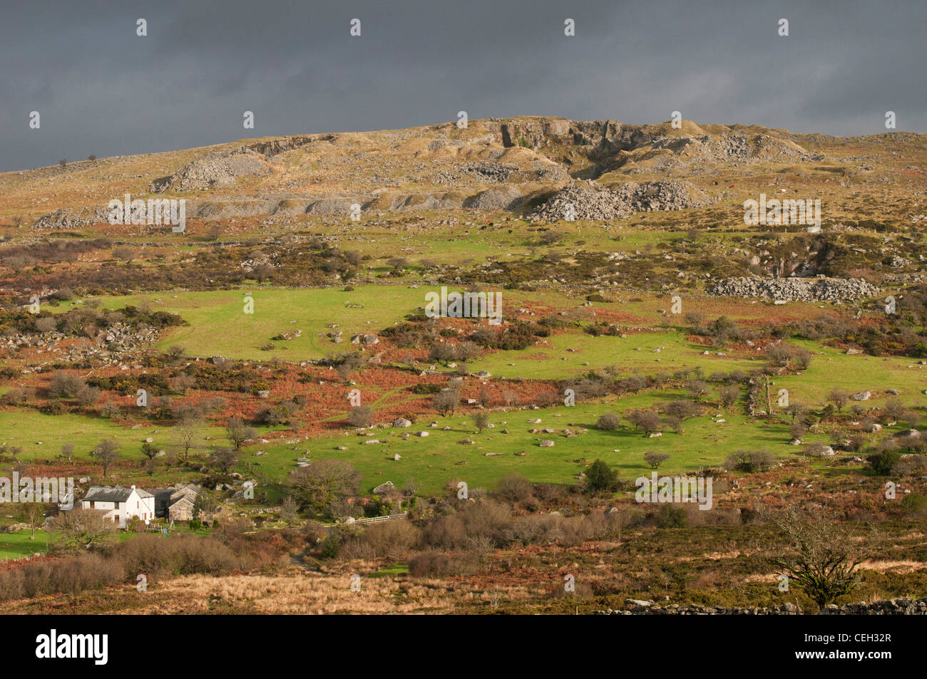 Swelltor quarry on Dartmoor in autumn with isolated farmhouse at the base of the hill, Devon UK - Stock Image