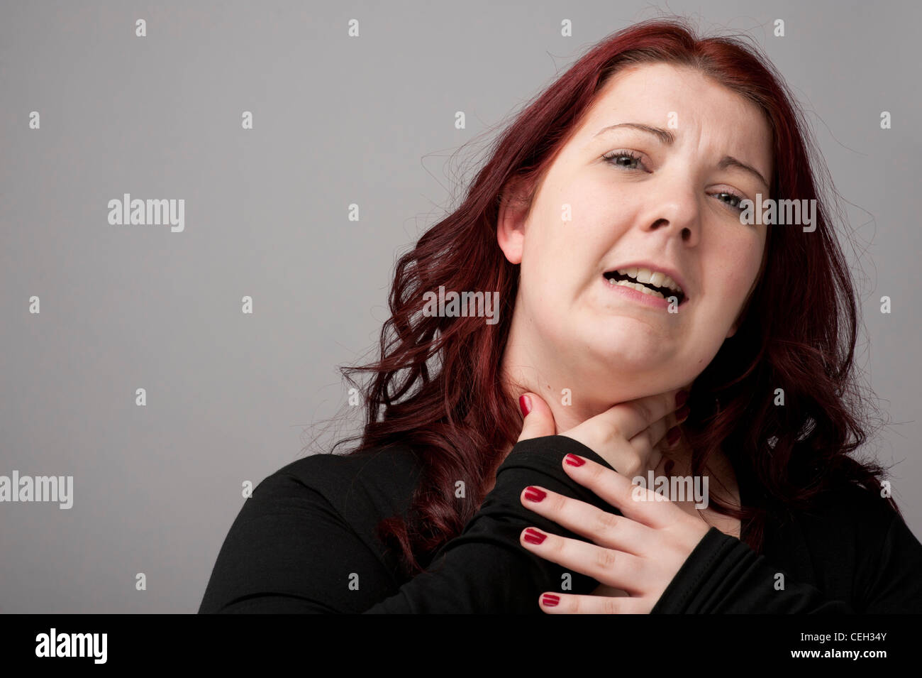 A auburn haired caucasian woman with a sore throat pain in the neck neckache - Stock Image