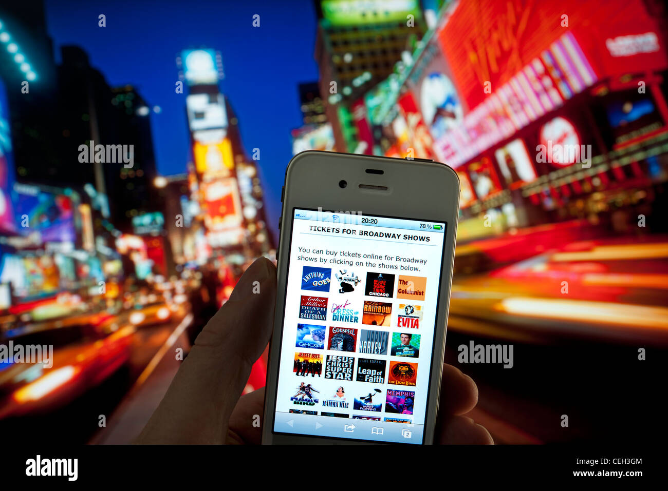Apple iPhone at dusk with screen displaying live on-line ticket purchase for Broadway theater shows Times Square - Stock Image