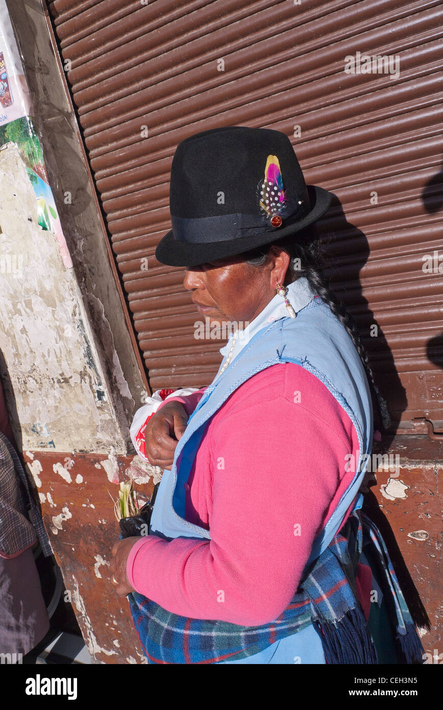 An indigenous Ecuadorian Indian woman in the traditional fedora hat and a blue apron stands on sidewalk in Latacunga, - Stock Image