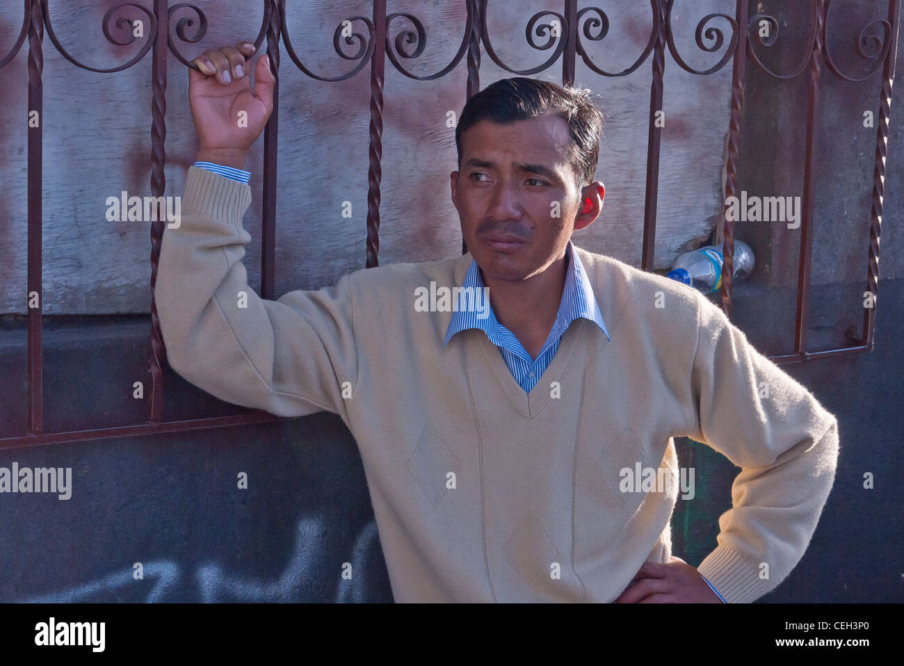 A 30-35 year old Hispanic male hangs onto a wrought iron fence about his shoulder waiting by the market in Latacunga, - Stock Image