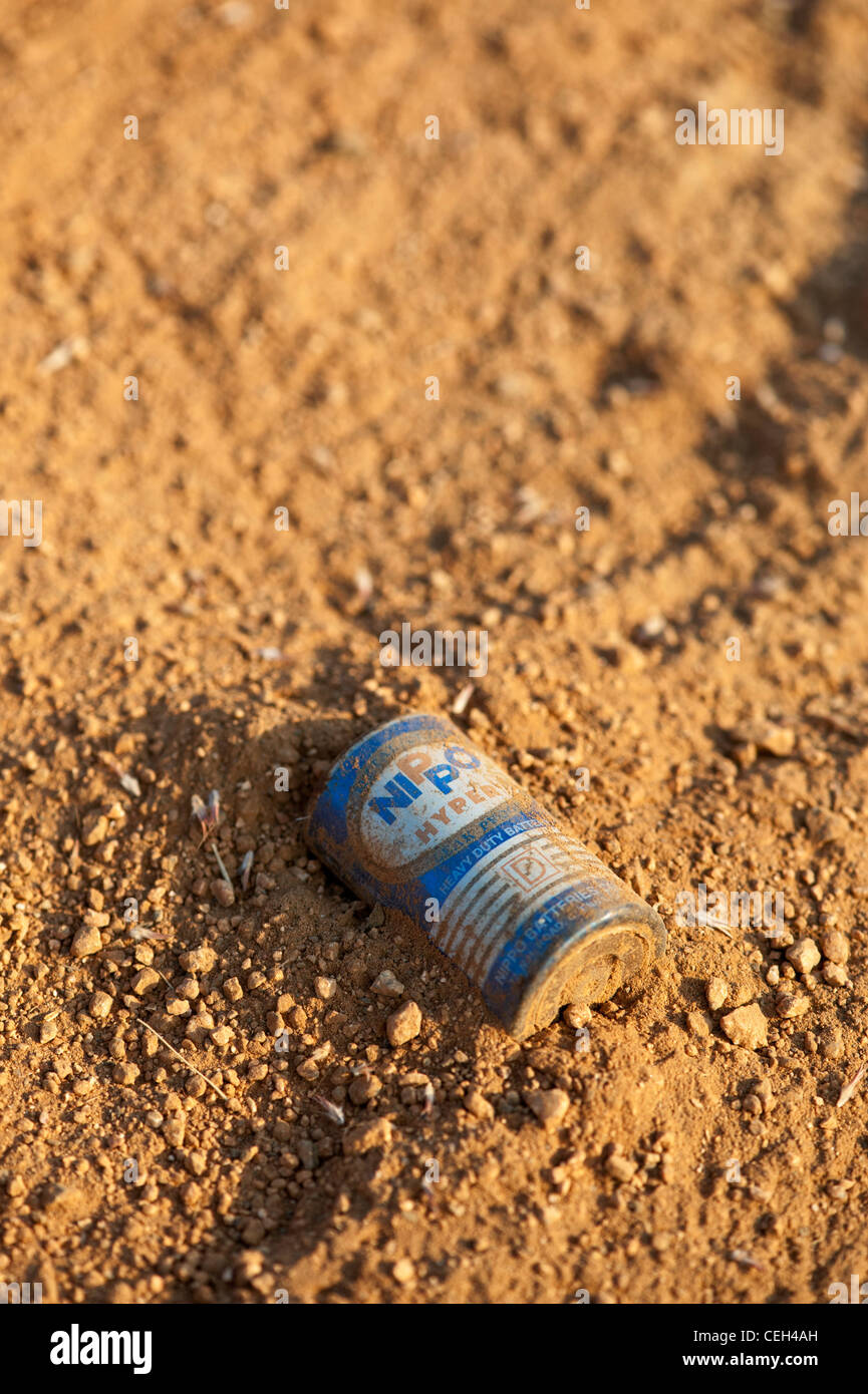 Discarded battery in the earth in the Indian countryside Stock Photo