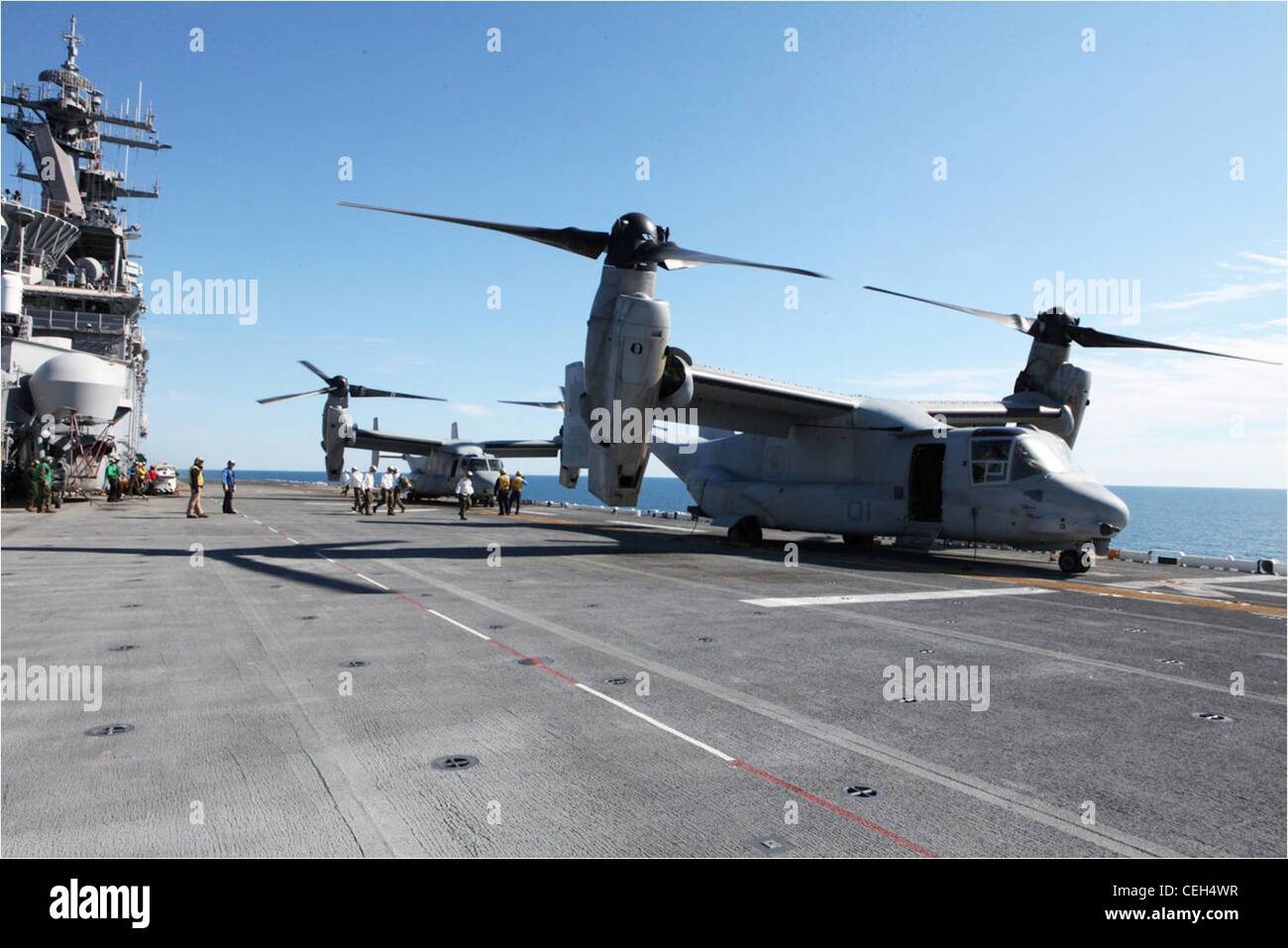 Marines and sailors unload gear brought aboard the USS Wasp by two MV-22B Ospreys from Marines with Marine Medium Stock Photo