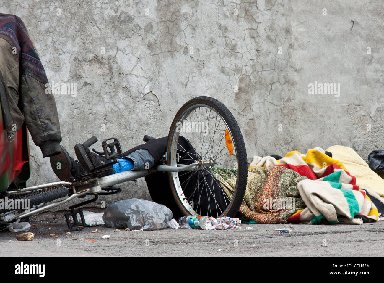 Homeless sleeping on the sidewalk guarding his bicycle with foots in front of a cracked wall surrounded by a lot - Stock Image