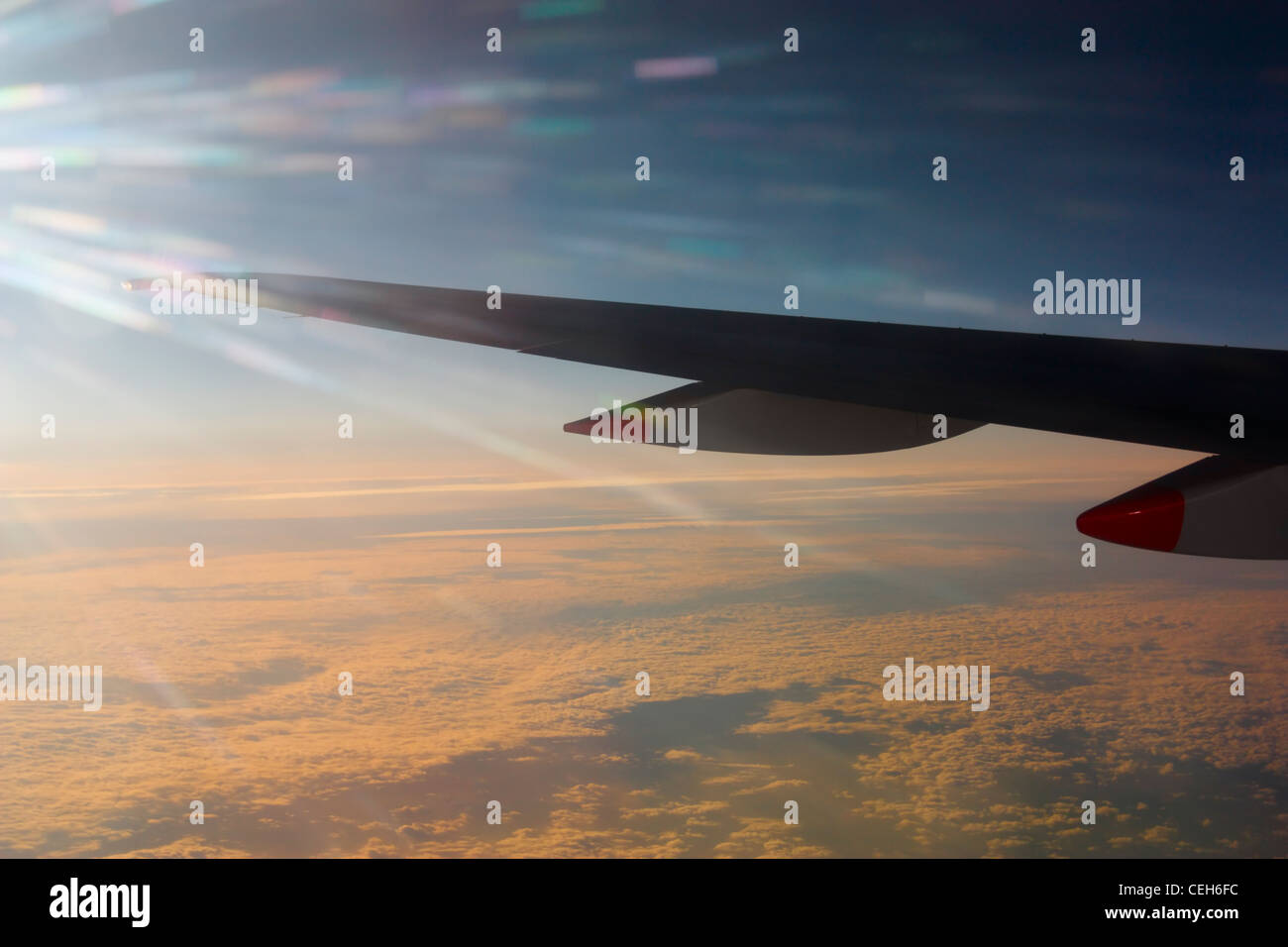 View from window seat of airplane wing over layer of cloud at sunset - Stock Image