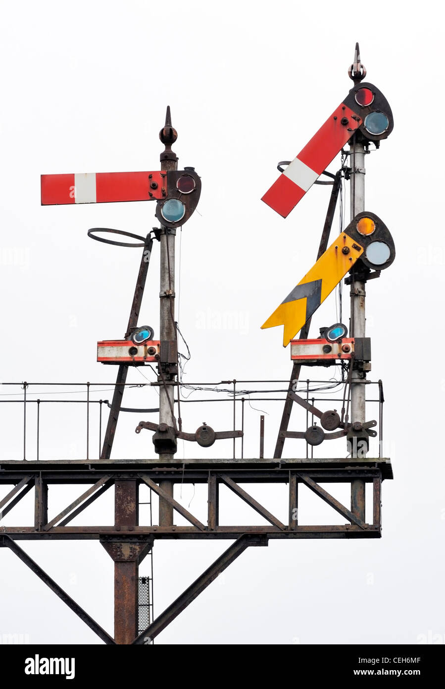 Closeup on traditional English semaphore railway signals on gantry on white background Stock Photo