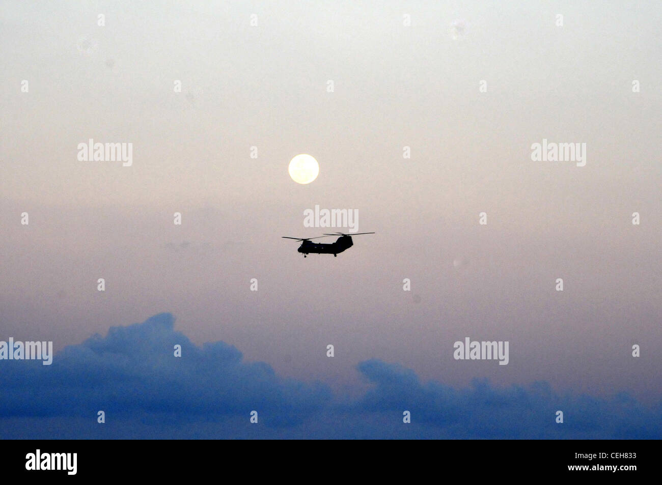 A full moon appears in the background as a Marine CH-46 Sea Knight helicopter performs deck landing qualifications - Stock Image