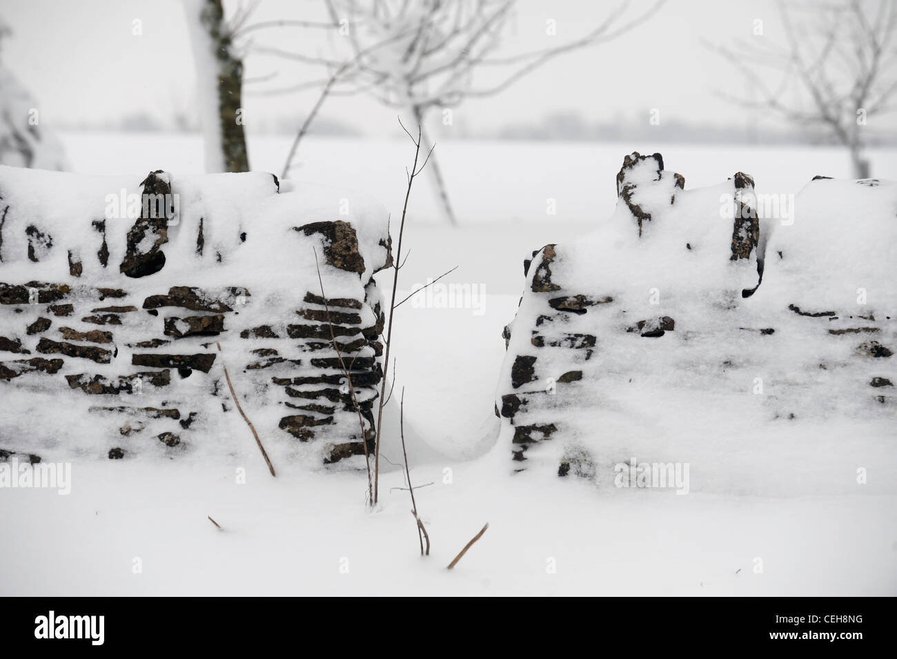 A gap in a cotswold stone wall in snowy conditions UK - Stock Image