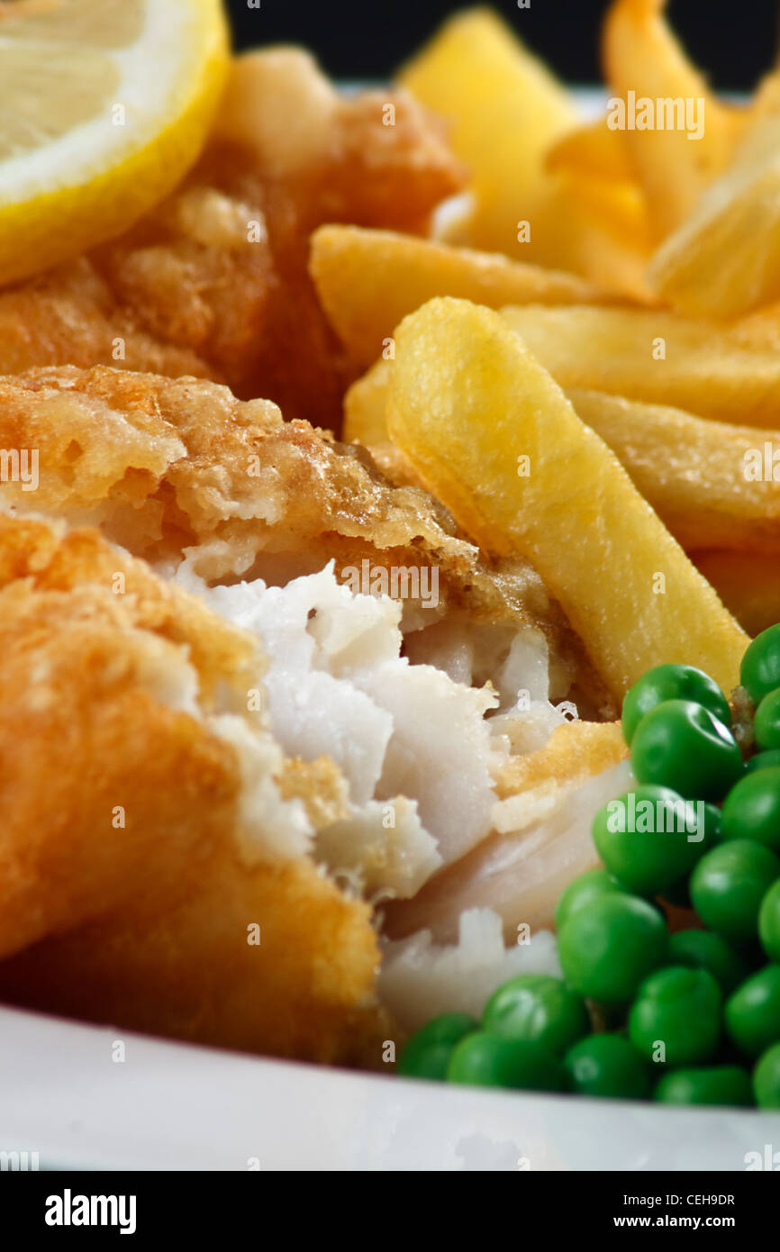Close up of fish and chips with peas and a slice of lemon. A traditional British Seaside Dish - Stock Image