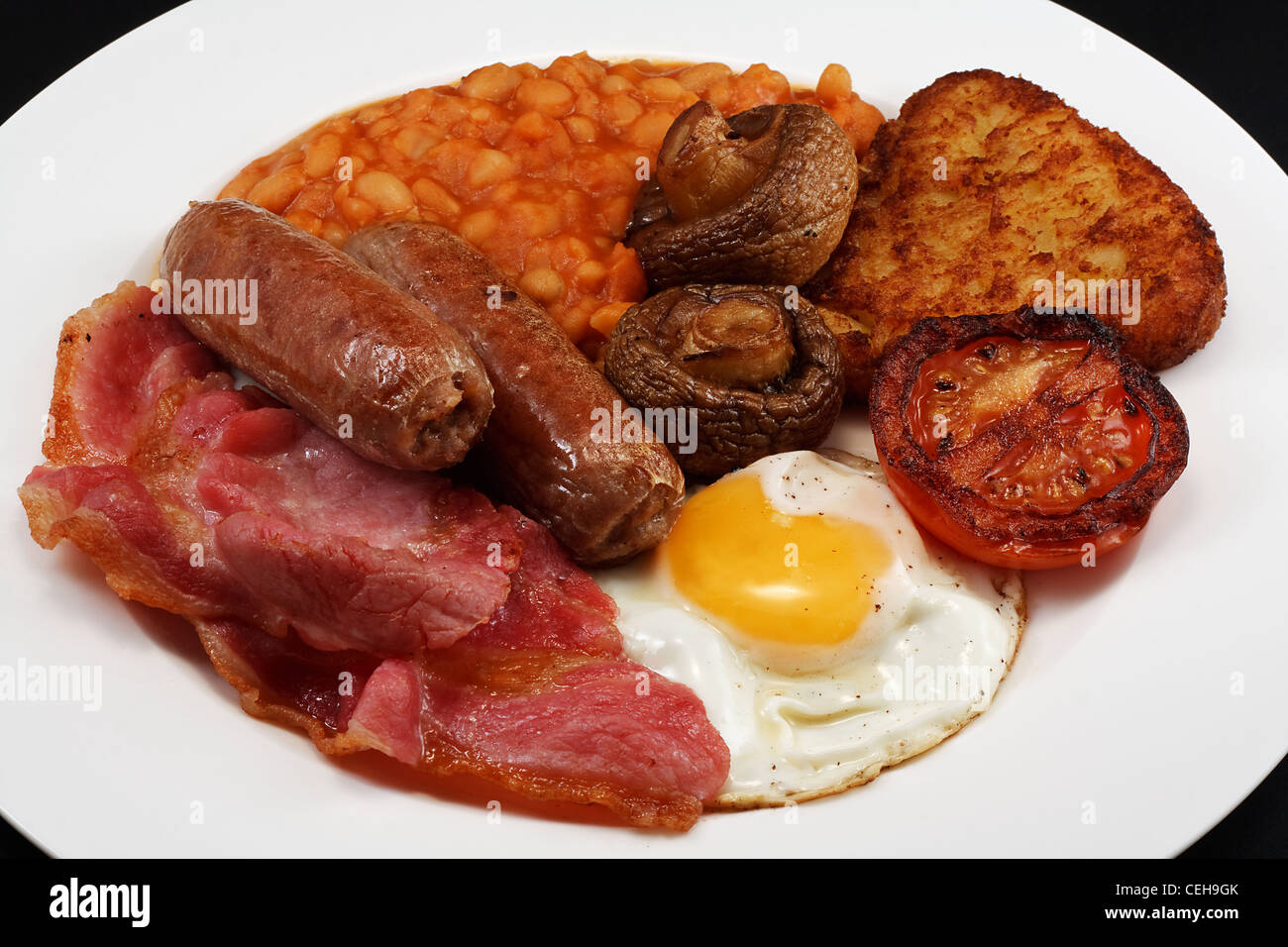 Typical fry up consisting of Sausage, bacon, egg, mushrooms, hash browns, beans and Fried Tomato Stock Photo
