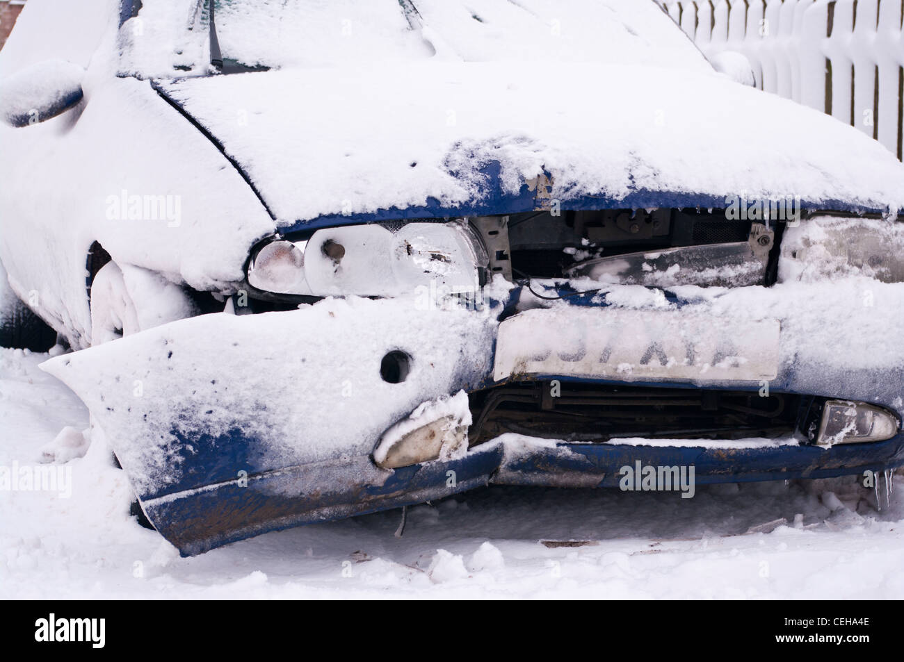 Damaged Dented Broken Down Car Vehicle After an Accident In The Snow Winter UK - Stock Image