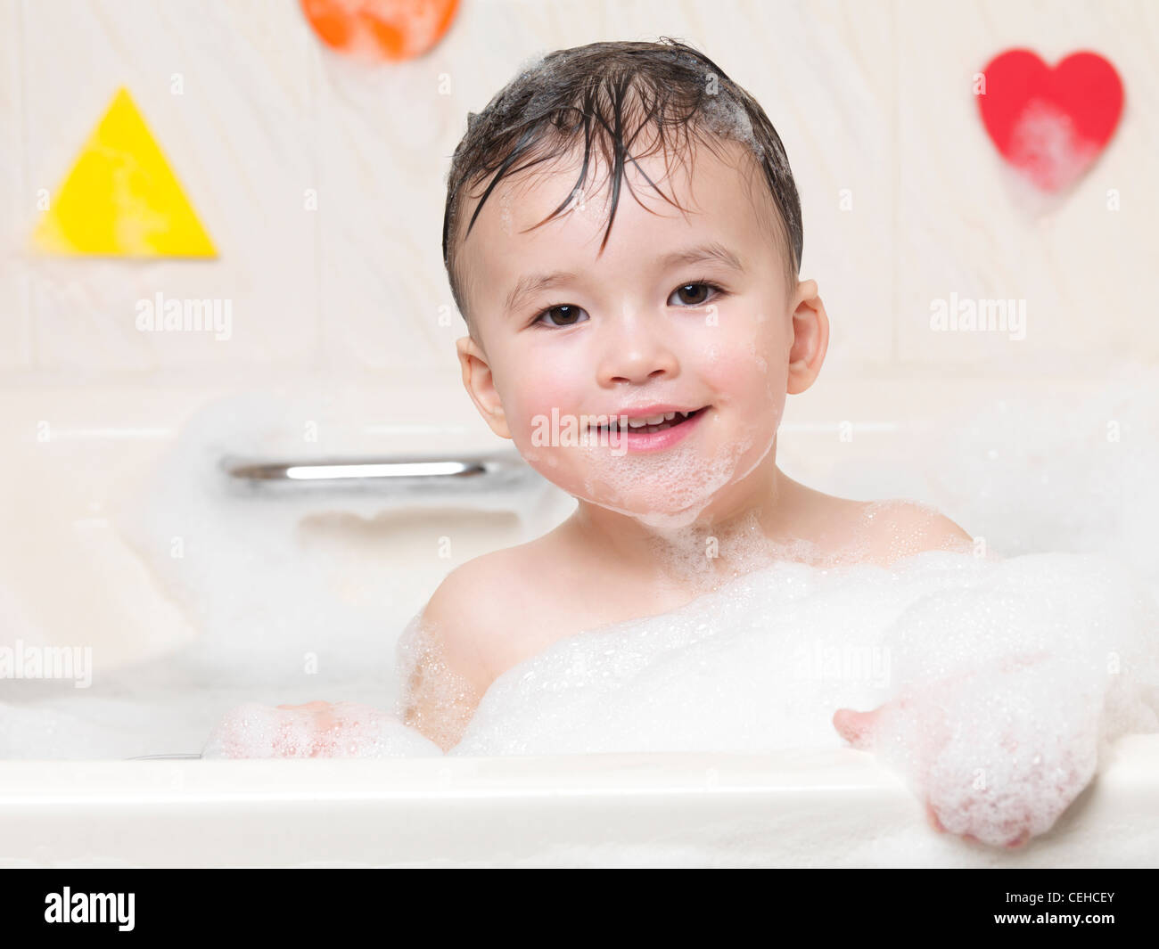 Cute smiling two year old child enjoying a bubble bath - Stock Image